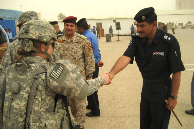 Soldiers from 4th Battalion, 6th Infantry Regiment meet with police training academy instructors following the July 30 graduation ceremony. The battalion is deployed from Fort Bliss, Texas to advise and assist in training Iraqi security forces in Maysan.