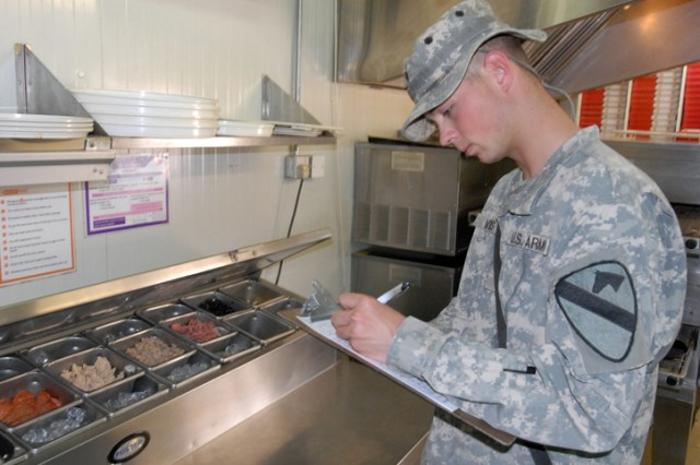 Spc. Jeffrey Davis, a Springfield, Mo., native and a preventive health specialist with Company C, 15th Brigade Support Battalion, 2nd Brigade Combat Team,1st Cavalry Division, examines a food preparation table at a food vendor on Forward Operating Base Warrior, Kirkuk, Iraq, July 27. Davis and his team are responsible for making sure vendors are using proper sanitation techniques while preparing food.