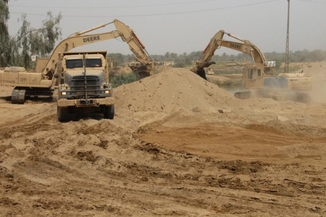TAJI, Iraq - Dump trucks and hydraulic excavators remove some of the 6,000 cubic yards of dirt to prepare the banks of the Tigris for a Mabey Johnson Float Bridge. The 277th Engineer Company, 46th Engineer Battalion, 225th Engineer Brigade is in charge of moving the dirt and the 555th Engineer Brigade will install the bridge with help from the Iraqi Army Engineers.
