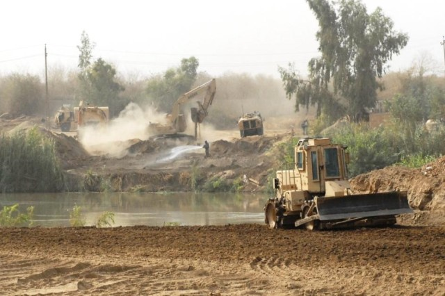 TAJI, Iraq - The Soldiers of 277th Engineer Company, 46th Engineer Battalion, 225th Engineer Brigade, work on the first step of a many step process to build a Mabey Johnson Float Bridge near Taji, Iraq. The huge undertaking requires 6,000 cubic yards of dirt to be moved to level the ground for the bridge. That is nearly 400 dump truck loads of dirt.