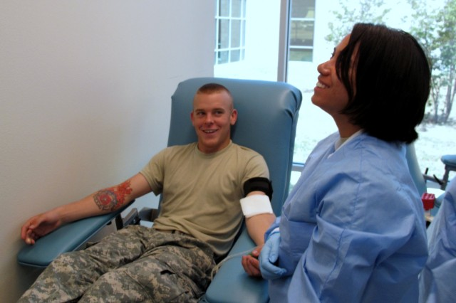 Pvt. Collin Stewart shows off his tattoo while Spc. Heather Walden prepares his arm for a blood donation at the Robertson Blood Center, Fort Hood, july 8, 2009.