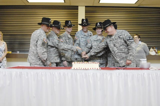 """Leaders assigned to the 4th Brigade Combat Team, 1st Cavalry Division """"Long Knives"""" cut the ceremonial cake at the reception of the unit's change-of-command ceremony at Fort Hood's 1st Cav. Div. Headquarters Aug. 6."""