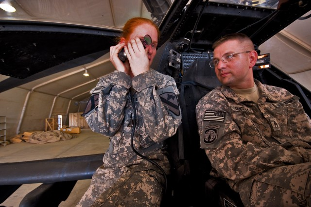 While going through various components of an AH-64D Apache attack helicopter, 1st Lt. Carolyn Wagnild (left), from Boise, Idaho, an Apache pilot in Company C, 1st Battalion, 227th Aviation Regiment, 1st Air Cavalry Brigade, 1st Cavalry Division, explains how the sighting system of the Apache works to Sgt.1st Class Jonathan Duffey, from Troy, Ohio, the tactical operations center noncommissioned officer in charge for 2nd Battalion, 107th Cavalry Regiment of the Ohio National Guard, Camp Taji, Iraq, Aug 10. The meeting between the two units is meant to build trust and understanding between the two units.