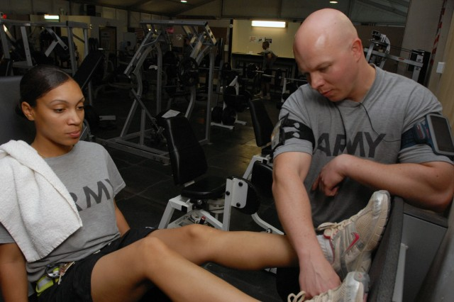 BAGHDAD - Spc. Anika Sneed (left), a supply specialist from Newport News, Va., assigned to Company C, 299th Brigade Support Battalion, 2nd Brigade. Combat Team, 1st Infantry Division, performs leg presses under the watchful eye of Sgt. 1st Class Simon Robertson, from Brownsville, Texas, a physical therapy technician assigned to Co. C, 299th BSB, 2nd BCT, 1st Inf. Div. at Victory Base Complex, here, Aug. 10. Sneed is working out her knee as part of a physical therapy program initiated by Robertson, which prescribes safe exercises to strengthen muscles and rehabilitate injuries.