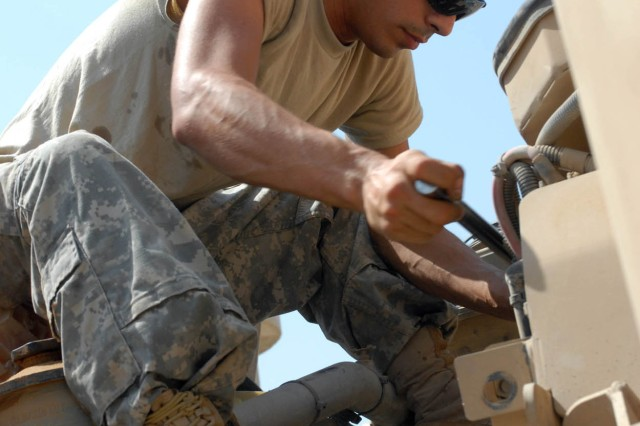 BAGHDAD - Houston, Texas native, Spc. Michael Saucier, a Bradley mechanic for A Company, 2nd Battalion, 5th Cavalry Regiment, 1st Brigade Combat Team, 1st Cavalry Division, checks and replaces the air filter on a Mine Resistant Ambush Protected vehicle Aug. 11 as a part of preventative maintenance checks and services.