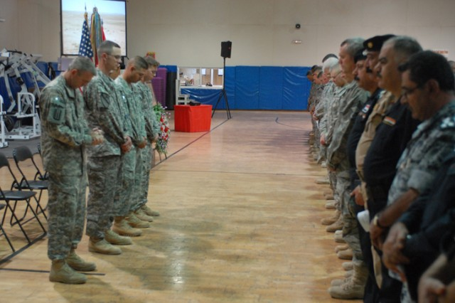 Soldiers, Airmen, Iraqi Police, Iraqi Army and civilians bow their heads in remembrance of Sgt. 1st Class Johnny Polk during a memorial service in his honor at Forward Operating Base Warrior, Kirkuk, Iraq, August 8. Polk died July 31 from wounds sustained from a grenade attack that occurred in Kirkuk city, Iraq, July 23.