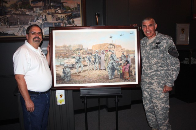Col. Philip Battaglia, former Commander of the 4th Brigade Combat Team, 1st Cavalry Division, turns the Long Knife 'Advise and Assist' Brigade Print over to Steven Draper, Director of the 1st Cavalry Division Museum on Aug. 12. The Brigade Print, symbolizes the 'Advise and Assist' mission the Long Knives had while working in Southern Iraq.