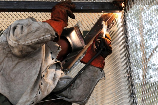 Pfc. Colby D. Herndon, from Dolthan, Ala., welds a hazardous material cage at the 514th Ordinance Company's Allied Trades metalworking shop.