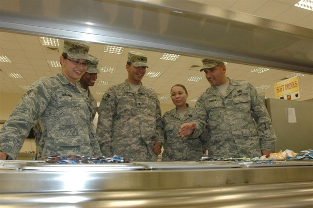 Senior Airman Naomi Magner, Senior Airman Angela Prince, Spc. Joseph Hillmert, Senior Airman Nastasskia Gerald, observe as Staff Sgt. Edwin Rivera, shows them the proper food layout at the new 72,000 square foot Mirage Dining Facility. The first dining facility in the Iraqi Theater staffed by both Soldiers and Airmen began daily operation this month here at Joint Base Balad