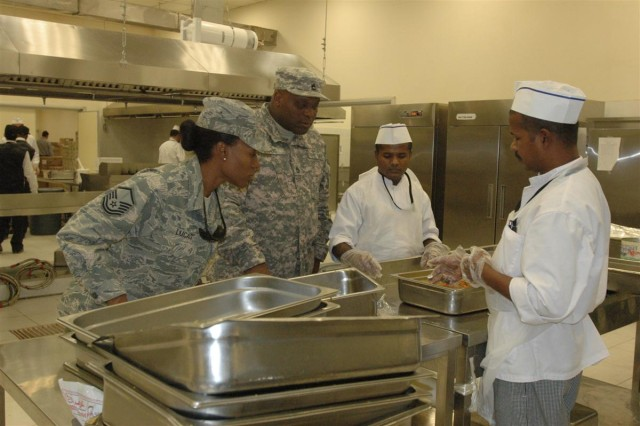 Master Sgt. Tilwanja Lucas, manager, Dining Facility 2, Sustainment Services Flight, 332nd Expeditionary Force Support Squadron, 332nd Air Expeditionary Wing, and Sgt. 1st Class Richard L. Grays, assistant manager, DFAC 2, 72nd Expeditionary Signal Battalion, check over the preparation of food at the 72,000 square foot Mirage Dining Facility at Joint Base Balad. It is the first dining facility in the Iraqi Theater staffed by both Soldiers and Airmen