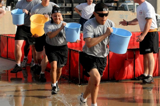 """Team El S-4 Spc. Osvaldo Martinez, Sgt. Bernice Macias, Spc. John Green and Staff Sgt. Joshua Sekutera, all from the 163d Military Intelligence Battalion, move out in line with buckets at the ready in the Bucket Brigade competition, where teams must douse a """"burning"""" house, as part of the Fire Muster that took place at Joint Base Balad Aug. 9. The event is complete when the water thrown from the buckets drains and fills a barrel"""