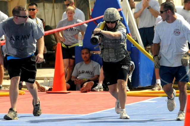 Spc. Kristina Heller, a Hamlake, Minn. native, with the 874th Human Resources Company, drags a fire hose down the length of a basket ball court during the Fire Fighter's Combat Challenge, during the Fire Muster at Joint Base Balad Aug. 9