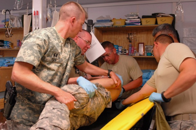 Capt. Charles Day, surgeon, 2nd Battalion, 87th Infantry Regiment, 3rd Brigade Combat Team, 10th Mountain Division, assists clockwise, Spc. Frank Romanowski and Spc. Timothy Currie, in rolling Pfc. Nicholas Henrich, a Fairborn, Ohio, native. Pfc. Robert Shipley checks Henrich's spine prior to placing him on a backboard during their Emergency Medical Technician recertification training at Forward Operating Base Airborne, Aug. 8. (Photo by U.S. Army Sgt. Rob Frazier, 5th Mobile Public Affairs Detachment)