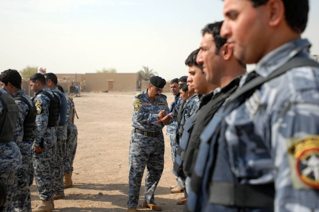 """BAGHDAD - The 2nd Federal Police Brigade commander (left) examines each Federal Policemen individually to ensure they are within the uniform regulation as part of the Wolf Academy at Joint Security Station Istiqlaal Aug. 12. Soldiers from Troop C, 1st """"Garryowen"""" Squadron, 7th Cavalry Regiment, 1st """"Ironhorse"""" Brigade Combat Team, 1st Cavalry Division, held courses on safety techniques during a vehicle rollover for the the 1st and 2nd Battalion, 2nd Federal Police Brigade."""
