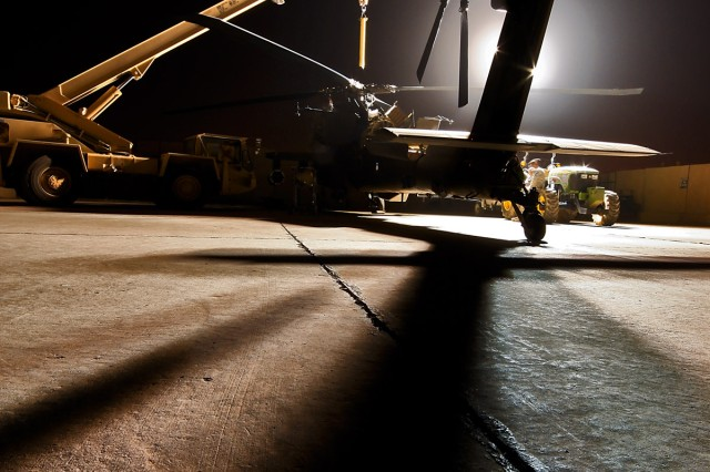 CAMP TAJI, Iraq-Working through the night under utility lights, AH-64D Apache attack helicopter crew chiefs from 1st Battalion, 227th Aviation Regiment, 1st Air Cavalry Brigade, 1st Cavalry Division, Multi-National Division Baghdad, bring their equipment to the aircraft to conduct a main rotor head retorque, here, Aug. 13. For the 1st ACB, aviation operations take place around the clock - day and night.