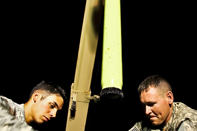 CAMP TAJI, Iraq-Spc. Christian Pino (left), from San Diego, and Spc. Josh Ramsey, from Pomona, Miss., both AH-64D Apache attack helicopter crew chiefs in 1st Battalion, 227th Aviation Regiment, 1st Air Cavalry Brigade, 1st Cavalry Division, Multi-National Division Baghdad, suspend the gear shaft in the air, giving acces to internal components of the main rotor head on an Apache, to complete work for a main rotor head retorque, here, Aug. 13. A retorque is a maintenance procedure that ensures the bolts on a rotor head are securely fastened and ready for prolonged flight.