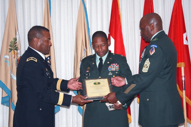 Brig. Gen. Jesse Cross, 50th Quartermaster General of the Army (left) and Command Sgt. Maj. Nathan Hunt, regimental command sergeant major, present a Distinguished Unit of the Regiment plaque to Col. Pharisse Berry (center), who accepted the award on behalf of the 1st Bn., 402nd AFSB.