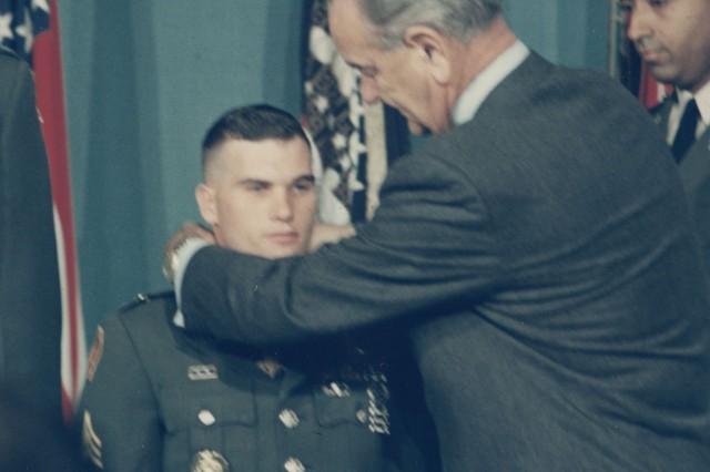 Retired Master Sgt. John Baker Jr. is awarded the Medal of Honor by President Lyndon Johnson in 1968 as his company commander, Capt. Robert Foley, looks on.