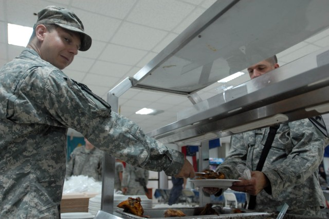 "BAGHDAD - Coldwater, Mich. native, Pfc. Justin DeWitt, a cook assigned to Forward Support Company E, 1st Battalion, 5th Cavalry Regiment, attached to the 1st ""Ironhorse"" Brigade Combat Team, 1st Cavalry Division, serves dinner, Aug. 16, at Joint Security Station War Eagle."