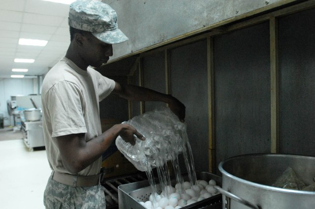 "BAGHDAD - Newport, R.I. native, Pfc. Andre Barrett, cook assigned to 1st Battalion, 5th Cavalry Regiment, attached to the 1st ""Ironhorse"" Brigade Combat Team, 1st Cavalry Division, pours water over eggs to boil them for breakfast, Aug. 18, at Joint Security Station War Eagle. The cooks at the ""Ironhorse"" Brigade dining facility try to create high quality meals with a homemade feel, said Barrett."