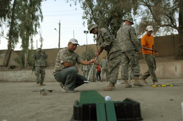 """BAGHDAD - Tampa, Fla. Native, Mike Sposa (left), one of the """"Fairways 2 Greens"""" golf pros, assists Rockingham, N.C. native Pvt. Anahi Padilla (right), human resource specialist assigned to Headquarters and Headquarters Troop, 1st Brigade Combat Team, 1st Cavalry Division with a putt at Joint Security Station War Eagle Aug. 18. Sposa and three other pros have visited camps around Kuwait and Iraq, helping Soldiers with putting, chipping and driving."""