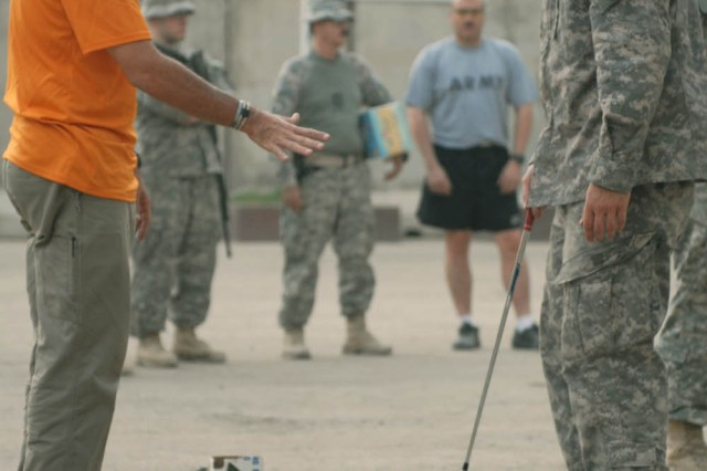 """BAGHDAD - Orlando, Fla. Native, Carl Paulson (left), a """"Fairways 2 Greens"""" Golf Tour golf pro, advises Flatwoods, Tenn. Native, Pfc. Andrew Bunch (right), an intelligence personnel specialist assigned to Company A, 1st Brigade Special Troops Battalion, 1st Brigade Combat Team, 1st Cavalry Division, on his chipping techniques during the """"Fairways 2 Greens"""" Golf Tour at Joint Security Station War Eagle Aug. 18."""