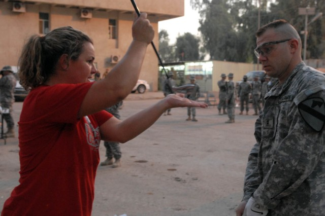 "BAGHDAD - Phoenix native, Becky Lucidi (left), a golf pro with the ""Fairways 2 Greens"" Golf Tour, demonstrates how to properly use a pitching wedge to Rio Rancho, N.M. native, Chief Warrant Officer Michael McMurray, the electronic warfare officer for Headquarters and Headquarters Troop, 1st Brigade Combat Team, 1st Cavalry Division, during the ""Fairways 2 Greens"" Golf Tour at Joint Security Station WarEagle Aug. 18"