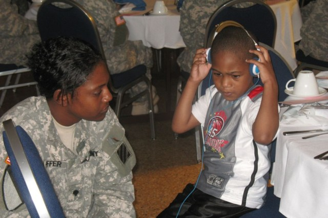 Spc. Shondalay Shaffer, Company B, 203rd Brigade Support Battalion, 3rd Heavy Brigade Combat Team, 3rd Infantry Division, keeps her son occupied during the brigade's Female Soldier Deployment Readiness Luncheon Aug. 19 at the Fort Benning, Ga. Community Club. The unit's female Soldiers gathered to gain information about issues concerning women during deployments.