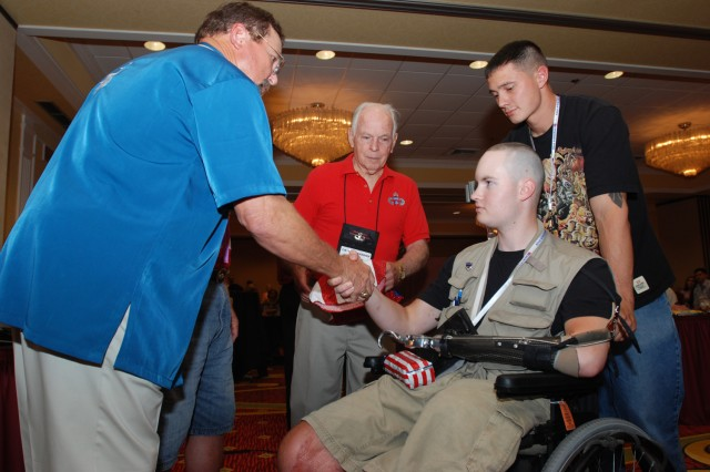 Sgt. John Hoxie (in wheelchair) receives a handshake from Carl Bludau, Chairman of the 82nd Airborne Division Wounded Warriors Program, during a dinner honoring Purple Heart recipients from Iraq and Afghanistan that was part of the Association's 63rd National Convention in Indianapolis, Ind. Aug. 19 - 22. Hoxie and 41 other wounded warriors were flown free of charge to Indianapolis by the association's members to take part in the convention. (U.S. Army photo by Staff Sgt. Mike Pryor, 2nd BCT, 82nd Abn. Div. Public Affairs)