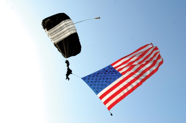 MSG Dale Warner, Silver Wings team leader, sky dives with the American flag during National Airborne Day festivities Friday.
