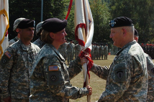 Gen. Carter F. Ham, the commanding general of U.S. Army Europe and Seventh Army, hands the colors of the 21st Theater Sustainment Command to its new commanding general, Brig. Gen. Patricia E. McQuistion, during the change of command ceremony at the sports field on Daenner Kaserne Aug. 20.