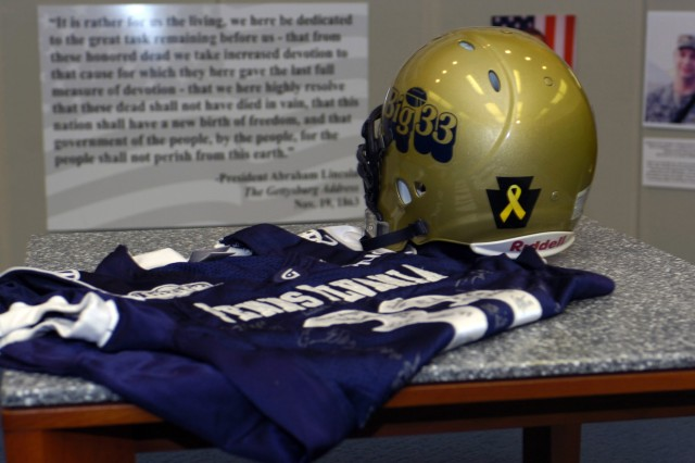 With President Abraham Lincoln's Gettysburg Address in the background, a jersey and helmet adorned with a tribute to Pennsylvania's 34 National Guard Soldiers killed in action stand reminders of sacrifice and remembrance.