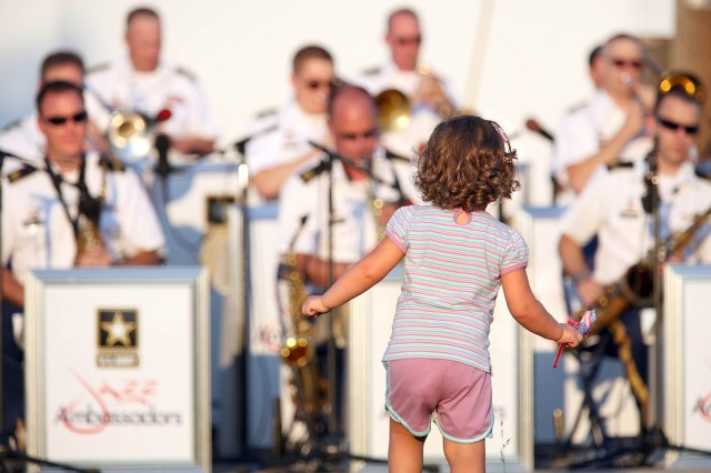 Two-year-old Grace Kiamie dances to the music of the United States Army Field Band's Jazz Ambassadors during the group's 40th anniversary concert Saturday evening at the Fort Meade Pavilion. The concert, which was part of the U.S. Army Field Band's annual summer series, paid tribute to The Studio Band, the predecessor of the Jazz Ambassadors.
