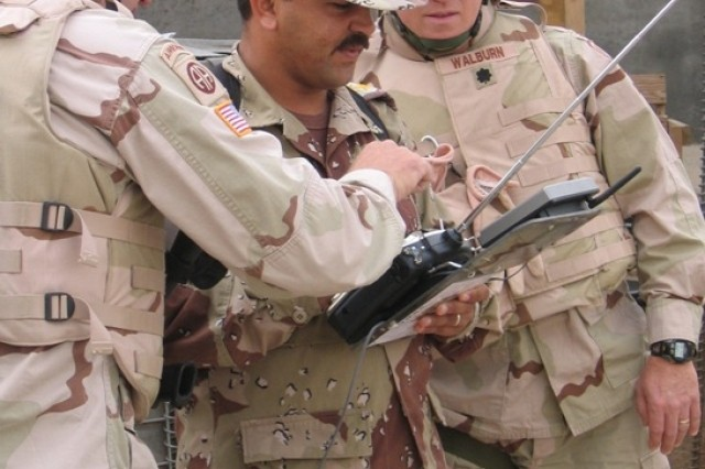 Active Guard Reserve Lt. Col. Dennis Walburn volunteered for duty in Iraq as part of the Army's Rapid Equipping Force. Walburn, far right, observes as an Iraqi soldier at Balad Air Base receives instruction on how to maneuver a Rapid Equipping Force robot.
