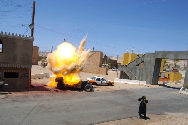 A simulated improvised explosive device explodes during a mass-trauma training exercise at Medina Wasl, a training village at the National Training Center on Fort Irwin, Calif. The 11th Armored Cavalry Regiment's new Mechanized Infantry Battalion will be set to use hybrid threat warfare on rotational training units in the near future. Hybrid threat warfare will employ conventional military assets with insurgency operations.