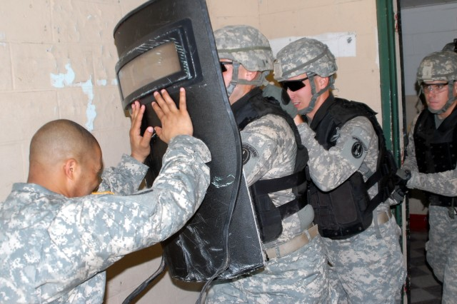 Soldiers from C Company of The Old Guard, charge a mock detainee during deployment training at the former Lorton Prison in Lorton, Va.