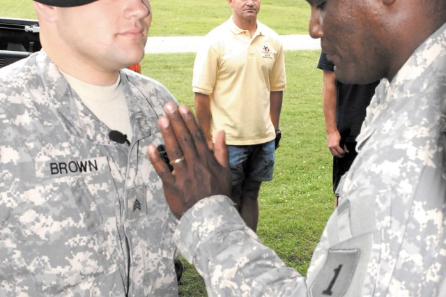 """Lt. Col. Gregory Gadson """"tacks on"""" the sergeant stripes he pinned on his battle buddy Sgt. Eric Brown, center, in an Aug. 6 ceremony at Aberdeen Proving Ground, Md."""