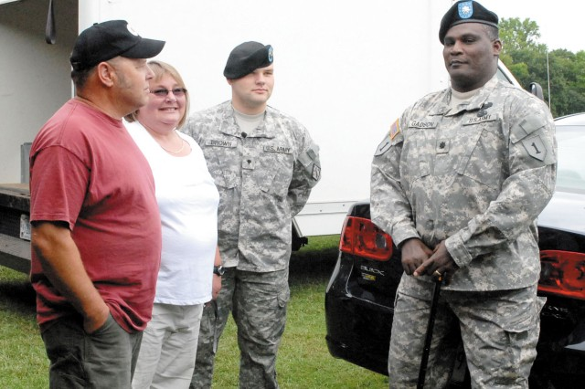 Lt. Col. Gregory Gadson, right, promoted his battle buddy Sgt. Eric Brown, center, in an Aug. 6 ceremony at Aberdeen Proving Ground, Md.  Brown's parents, Steve and Kathy Brown, left, traveled from their home in Usk, Wash., to attend the event.