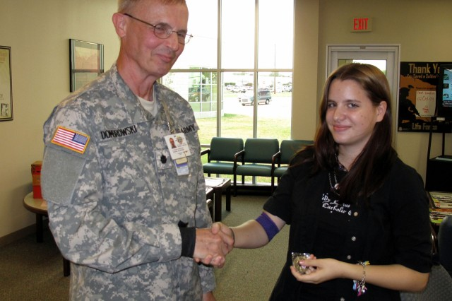 LTC Dennis Dombrowski, director of the Robertson Blood Center at Fort Hood, presents Jessica Zachar with a military coin. Thursday, August 6, 2009.