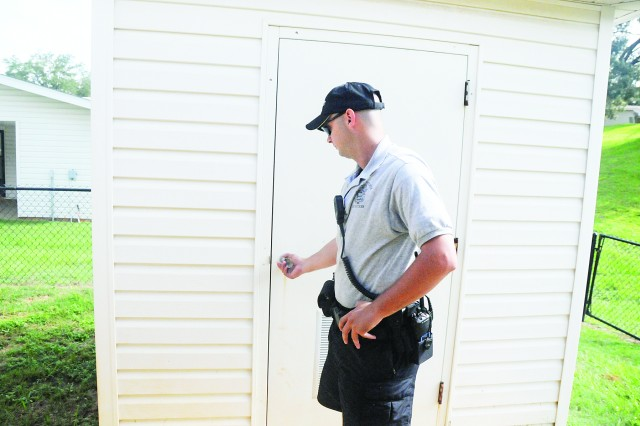 Community Police officer Spc. Rayford Ivey makes sure a storage shed is locked Tuesday during a courtesy check. These checks help ensure property stays protected while post residents are on vacation, temporary duty or emergency leave.