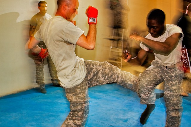 CAMP TAJI, Iraq-Training for a combatives tournament, Sgt. Jeremiah Bond (left), from Anacoca, La., a light wheeled vehicle mechanic in, Headquarters Support Company, 615th Aviation Support Battalion, 1st Air Cavalry Brigade, 1st Cavalry Division, Multi-National Division - Baghdad, launches out with a kick that Pfc. Malcom Knox, from New York City, a unit supply specialist in HSC, 615th ASB, effectively checks during a training session, here, Aug. 20.  Both part of Team Highlander, they'll compete in a combatives tournament to be held Aug. 29.