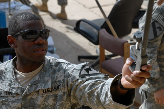 """CAMP TAJI, Iraq - Houston native, Sgt. Everson Lofton, a noncommissioned officer in charge of supply assigned to Battery A, 1st Battalion, 82nd Field Artillery Regiment, 1st Brigade Combat Team, 1st Cavalry Division, grabs a tool from a truck as he works hand-in-hand with other """"Dragon"""" troops, here Aug. 22."""