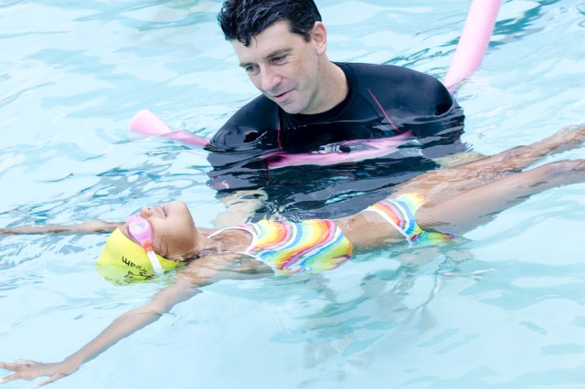 Oscar Roverato, instructor at the Flying Fish Swim Camp, helps Nevaeh Blanks learn to float on her back. The camp took place Aug. 3 through 7 at the Normandy Pool on Fort Bragg.