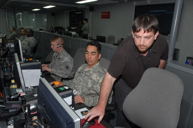 Sgt. Patrick Frye, left, Staff Sgt. Ted Janado, and Judd Tritt, 8th Theater Sustainment Command, monitor the flow of information during the day shift at the U.S. Army Japan Command Center, Aug. 18.