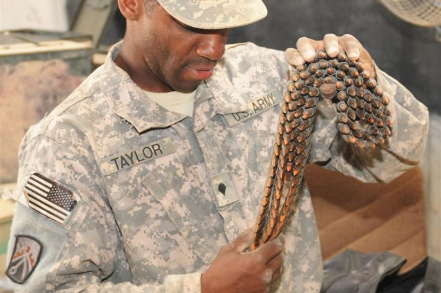 Spc. Angelo Taylor, a 23rd Ordnance Company heavy equipment operator and Memphis, Tenn. native, inspects rounds of ammunition to determine their serviceability. Serviceable ammunition gets repackaged and sent to Kuwait or Afghanistan.