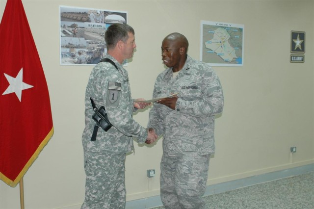 Brig. Gen. Paul L. Wentz, commanding general of the 13th Sustainment Command (Expeditionary), presents Capt. Cedric L. Finnen, operations officer with Task Force 586, with a certificate of appreciation in recognition of the task force's accomplishments during their six-month tour in support of Operation Iraqi Freedom. TF 586 has identified, collected and redistributed $50 million in excess supplies since February.