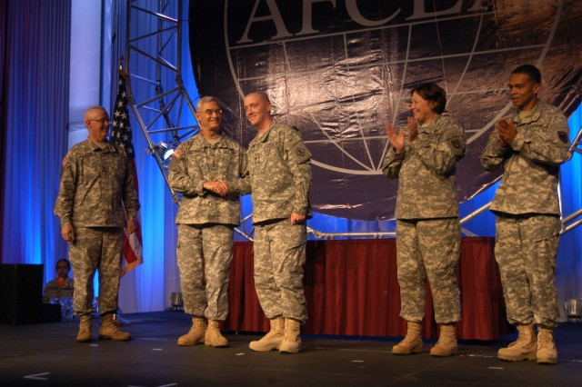 The Network Enterprise Technology Command/9th Signal Command (A) Soldier of the Year, Spc. Daniel Justice, 2nd Signal Brigade, 5th Signal Command, is congratulated with a coin from Lt. Gen. Jeffery Sorenson, U.S. Army Chief Information Officer/G-6, Aug. 20, during the LandWarNet Conference in Fort Lauderdale, Fla.