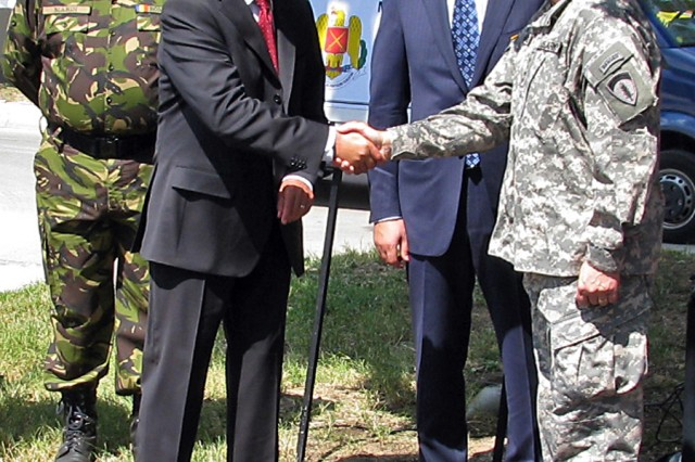 The president of Romania, Traian Basescu, shakes hands with U.S. Army Gen. Carter F. Ham (right) today at Mihail Kogalniceanu Airfield, Romania.  Chairman of the Romanian Joint Chiefs of Staff, Adm. Gheorghe Marin, PhD (left), and Romanian Minister of National Defense, Mihai Stanisoara (second from right) and Ham visited the training area to learn more about Joint Task Force-East.