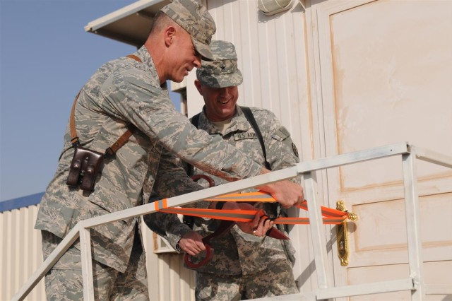 The 13th Sustainment Command (Expedtionary) Commanding General Brig. Gen. Paul L. Wentz and Air Force Brig. Gen. Craig A. Franklin, commander of the 332nd Air Expeditionary Wing, cut a ribbon to signify the opening of Red River Place Aug. 17 at Joint Base Balad.