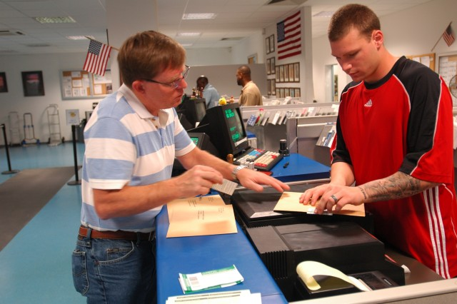 William Jessip asks Richard Ranno, a postal finance clerk, about delivery confirmation on a letter Aug. 14 at the Heidelberg Community Support Center post office. Ranno, who medically retired from the Army Aug. 21, is the first wounded warrior to be hired in Europe with the assistance of the Army Wounded Warrior program.